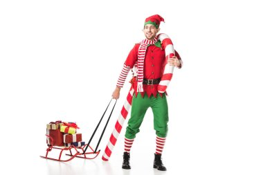 happy man in christmas elf costume carrying sleigh with presents and big candy cane isolated on white