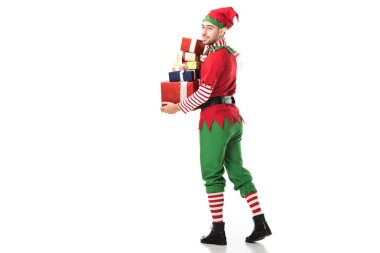 happy man in christmas elf costume looking at camera and carrying pile of presents isolated on white