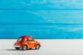 Nahaufnahme von rotem Spielzeugauto auf blauem Holzhintergrund