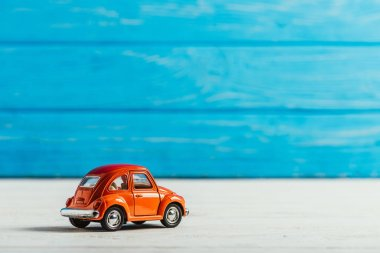 close-up shot of red toy car on blue wooden background
