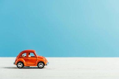 mavi zemin üzerine beyaz yüzey üzerinde sürme oyuncak kırmızı araba yan görünüm