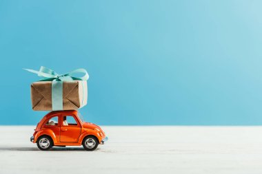 side view of toy red car with christmas gift box riding on white surface on blue background