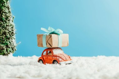 close-up shot of toy red car with christmas gift box riding by snow made of cotton on blue background