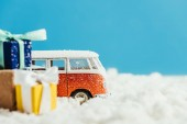 Fotografie close-up shot of toy van with christmas gifts standing on snow on blue background