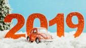Fotografie velký červený 2019 čísla s hračka auto stojící na sněhu na modrém pozadí, nový rok koncepce