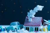 közeli lövés miniatűr autó ház éjszakában hóval és karácsonyi ajándékok