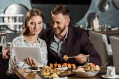 Fotografia Coppie attraenti per mezzo della compressa digitale mentre si mangia sushi nel ristorante