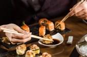 abgeschnittene Ansicht von Menschen, die im Restaurant Sushi mit Stäbchen essen