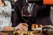 Ausgeschnittene Ansicht eines Mannes, der in Restaurant Rotwein in Glas einschenkt