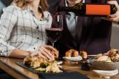 Teilansicht eines Mannes, der Rotwein ins Glas gießt, während Paar im Restaurant zu Abend isst