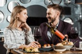 Photo Handsome Man offering his girlfriend wine while they having dinner in restaurant