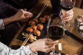 Teilansicht eines Paares, das sich Händchen hält, während es Wein trinkt und im Restaurant Sushi isst