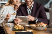Cropped view of couple using digital device while eating sushi in restaurant