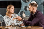 attraktives junges erwachsenes Paar hält Händchen, während es im Restaurant sitzt