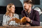 Schönes Paar, das sich beim Abhalten des Menüs im Restaurant anschaut
