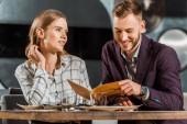 glückliches lächelndes Paar schaut in Speisekarte, um Abendessen im Restaurant zu bestellen