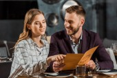 Frau zeigt auf etwas, während junges erwachsenes Paar in der Speisekarte sucht, um Abendessen im Restaurant zu bestellen