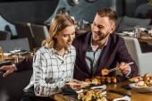 attraktive glückliche junge Erwachsene essen Sushi im Restaurant