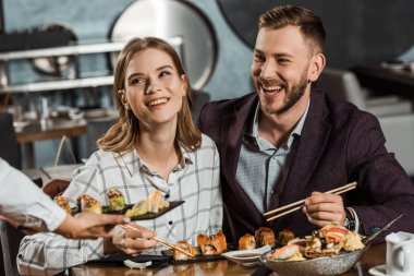 Smiling couple eating sushi rolls while waiter bringing new order in restaurant