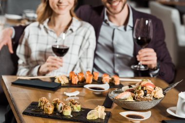 Partial view of smiling couple eating sushi and drinking wine in restaurant stock vector