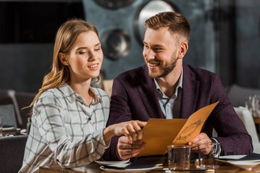 woman pointing at something while young adult couple looking in menu to order dinner in restaurant