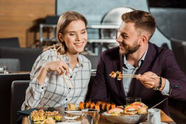 Attractive smiling couple eating together sushi rolls in restaurant