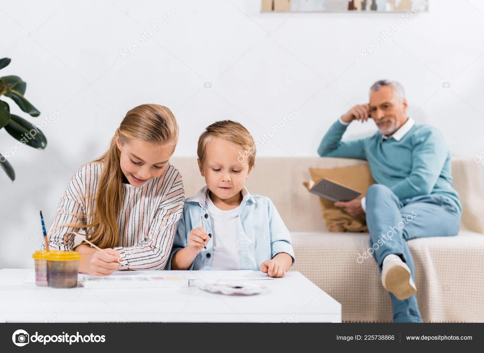 Tavolo Dietro Al Divano : Pittura tavolo mentre loro nonno che legge libro dietro divano