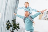 Fotografie laughing little kid sitting on grandfather shoulders and having fun at home