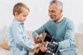 usmívající se středním věku člověk učí vnuk hraje na akustickou kytaru doma