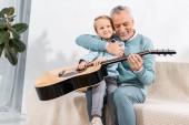 Selektivní fokus smějící se dědeček hrál s vnukem na kolena, hraje na akustickou kytaru doma