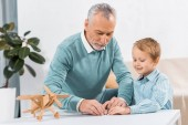 mature man making paper plane while his adorable grandson sitting near at table with wooden airplane