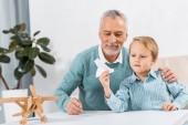 Muž středního věku a vnuk doma se baví s papírové letadlo