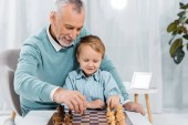 smiling middle aged man teaching grandson to play chess at home