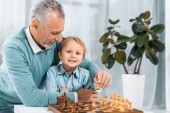 positive mature man playing chess with adorable grandson at home
