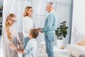Fotografia bambini holdings mani uno da altro mentre loro nonni in piedi dietro a casa sorridenti