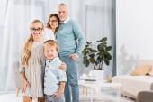 Selektivní fokus šťastných dětí všeobjímající při jejich prarodiče, stojící za doma
