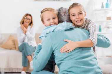 selective focus of smiling kids looking at camera and hugging grandfather at home