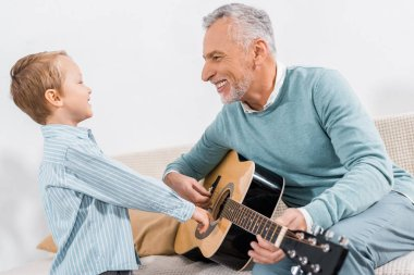 laughing middle aged man teaching grandson playing on acoustic guitar at home