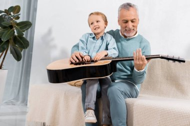 cheerful grandfather playing with grandson on knees playing on acoustic guitar at home