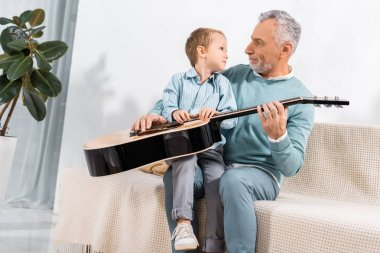 surprised grandfather with acoustic guitar looking at adorable little grandson on sofa at home