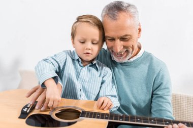 handsome grandfather playing with grandson on knees playing on acoustic guitar at home