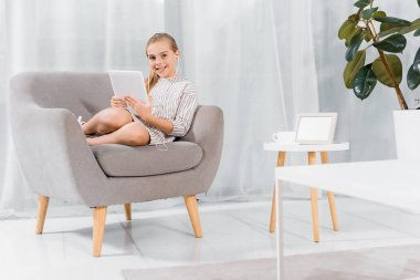 cheerful little child in earphones sitting on armchair with digital tablet at home