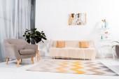 fuoco selettivo del salone moderno con moquette, divano e poltrona