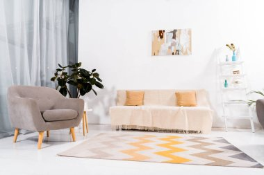 selective focus of of modern living room with carpet, sofa and armchair
