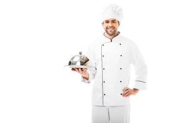 young chef holding serving plate with dome and looking at camera isolated on white