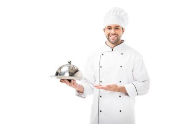 Happy young chef holding serving plate with dome and looking at camera isolated on white stock vector