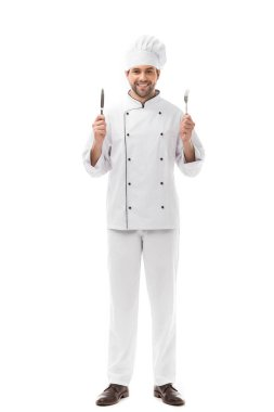 Smiling young chef holding knife and fork and looking at camera isolated on white stock vector