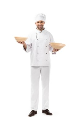 Smiling young chef holding bowls isolated on white stock vector