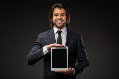 Handsome young businessman holding digital tablet with blank screen and smiling at camera isolated on black stock vector