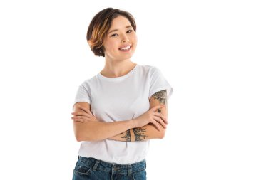 young woman with arms crossed looking at camera and smiling isolated on white